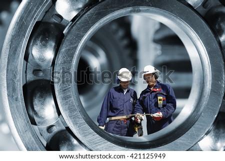 two mechanics, workers standing inside giant ball-bearing, steel industrial - stock photo
