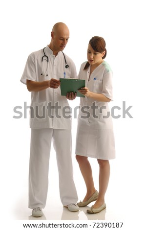 Two medical assistants reading notes about the patient