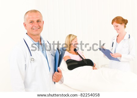 Two medical doctors professional with hospital patient lying in bed