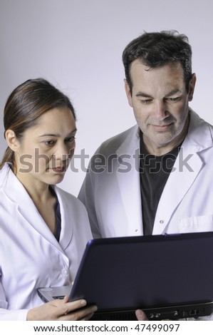 Two medical people looking at the laptop.Women is mixed race young lady. - stock photo