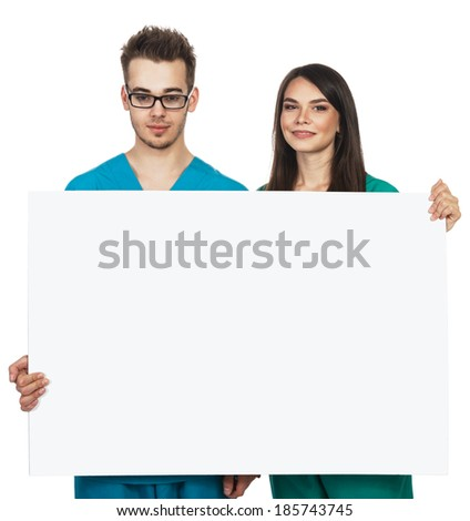 Two medical students / doctors / interns holding a blank sign - stock photo