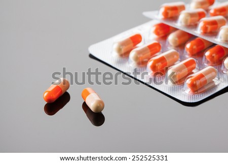 two medicine capsule drugs on reflective surface - stock photo