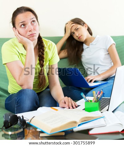 Two melancholy young student sitting on the couch and working on laptop computers. Focus on the left woman - stock photo