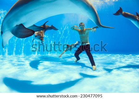 two men and three dolphin fooling around on the bottom of the dolphinarium - stock photo