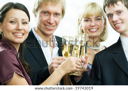Two men and two women stay in line, hold tumblers with champagne