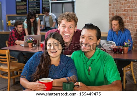 Two men and woman laughing in a cafe - stock photo