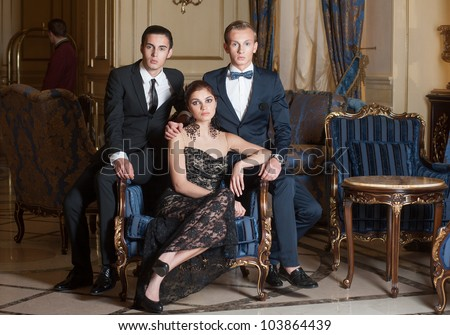 Two men and woman posing in luxury interior - stock photo