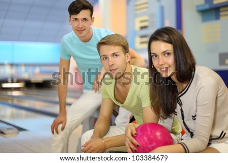 Two men and woman sit in bowling club; woman holds pink ball; focus on center man; shallow depth of field