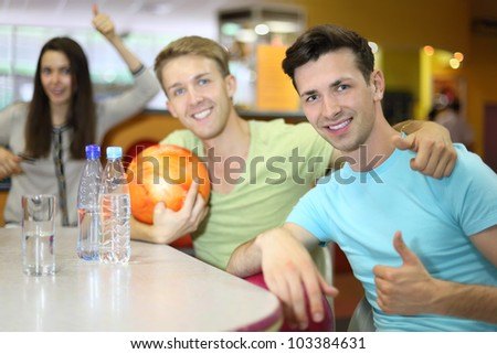 Two men and woman with balls sit at table in bowling and thumb up; bottles and glass with water on table; focus on right man; shallow depth of field - stock photo