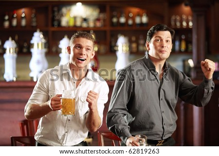 Two men are experiencing their favorite team and the pub - stock photo