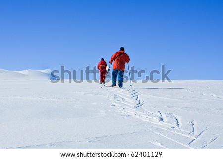 Two men are raised on a snow-covered hill