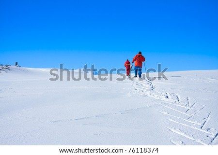 Two men are raised on a snow-covered hill in Antarctica - stock photo