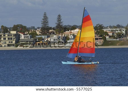 Two men are sailing a yacht with colorful sail in Mission Bay, San Diego, California. - stock photo