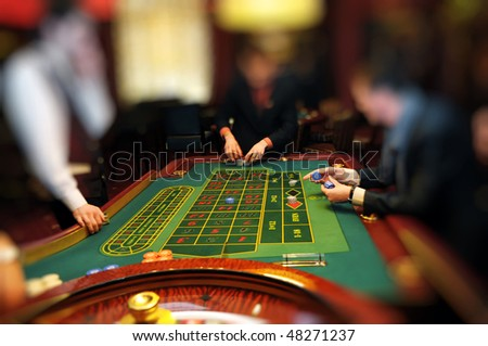Two men at gaming table collection chip placing bets in a casino assisted by a croupier. Focus is on table. Useful file for your new business, brochure or advertising - stock photo