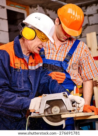 Two men  builder with circular saw. Brick wall in the background - stock photo