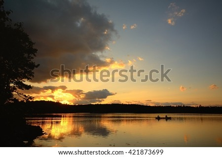 Two Men Canoeing at Sunset on a Wilderness Lake - stock photo