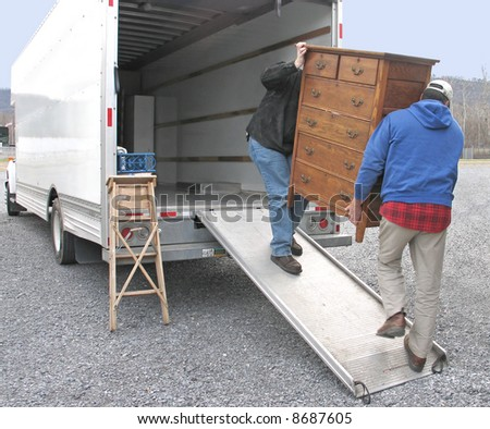 Two men carry chest of drawers onto a moving van - stock photo