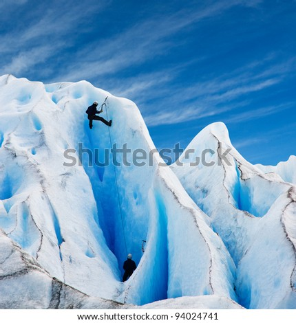 Two men climbing a glacier in patagonia. Copy space. - stock photo
