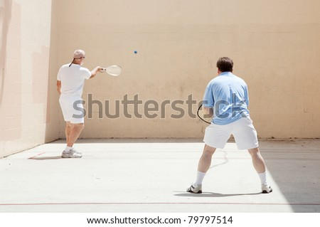 Two men, could be father and son, playing racquetball together. - stock photo