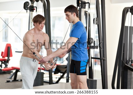 Two men doing exercise in the gym. Personal trainer - stock photo