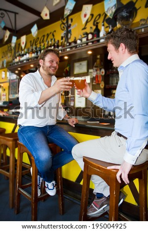 Two men drinking beer in bar - stock photo