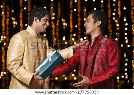 Two men exchanging gifts - stock photo