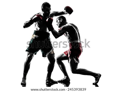 two  men exercising thai boxing in silhouette studio on white background - stock photo