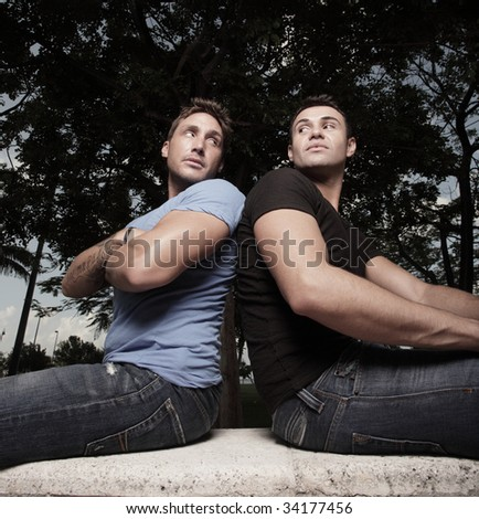 Two men facing away and glancing towards each other - stock photo
