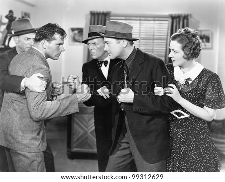 Two men fighting with each other and being held back by a woman and a man - stock photo