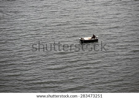 Two men fishing from a small boat in Littlebelt, Denmark - stock photo