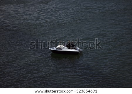 Two men floating in a boat and fishing on Little Belt in Denmark - stock photo