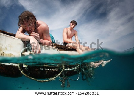 Two men floating in a sea with sad faces - stock photo
