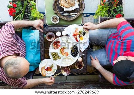 Two men having a discussion over a healthy fresh Turkish style breakfast as they sit outdoors at a table on a patio together, overhead view - stock photo