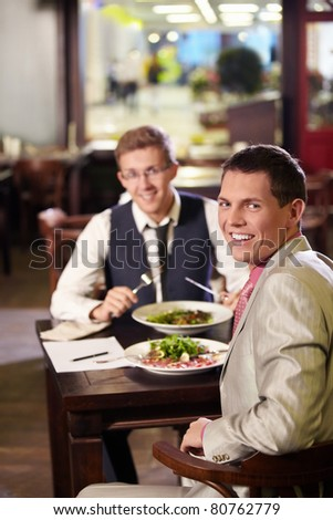 Two men having lunch in a restaurant - stock photo