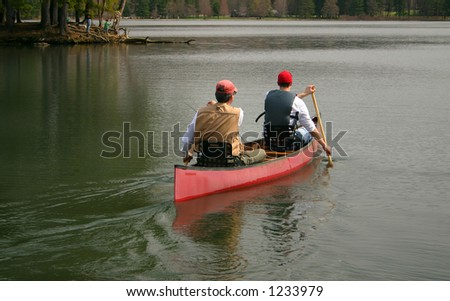 two men head out for a day of fishing in their canoe - stock photo