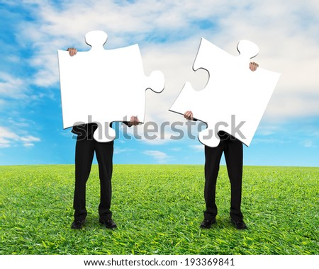 Two men holding blank puzzles on grass ground with blue sky - stock photo