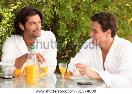 Two men housemates having breakfast outdoors - stock photo