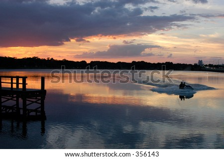 Two men in a boat are coming in at sunset creating a wake in the glassy reflection of the sky. - stock photo
