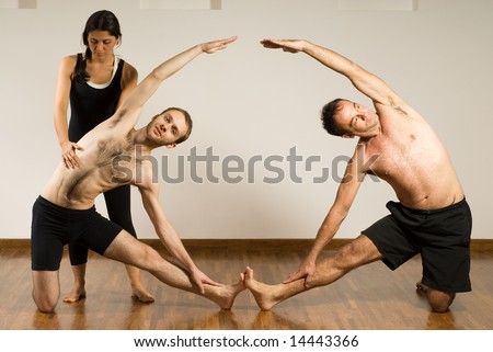 Two Men In A Yoga Class Their Feet Are Touching And Arms Arched