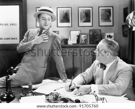 Two men in an office talking with each other - stock photo