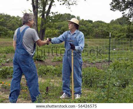 two men in bib overalls greet each other in a garden with a handshake