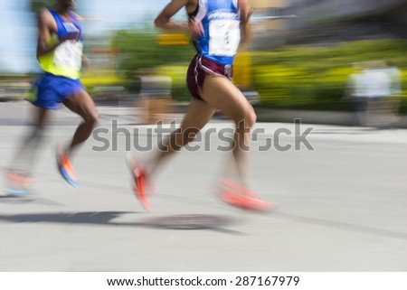 Two men in blurred motion in running competition - stock photo