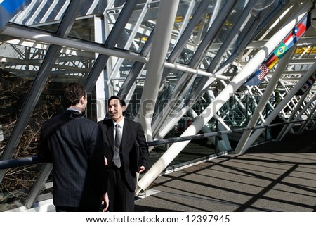 Two men in business suits chatting in an urban walkway on a sunny day - stock photo