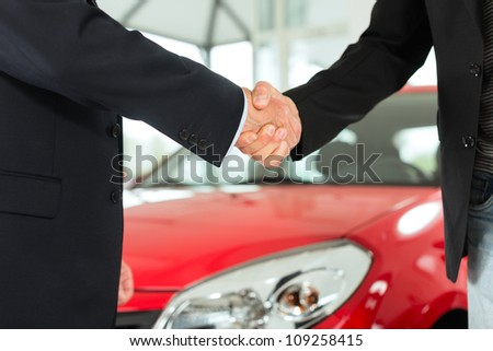 Two men in business suits shaking hands after a successful car purchase - stock photo