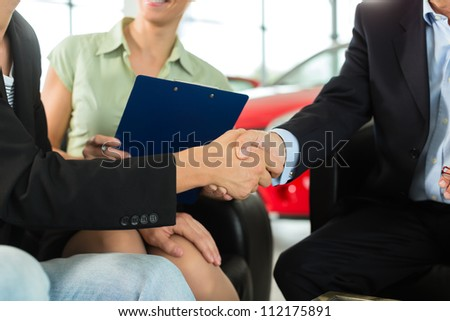 Two men in business suits shaking hands after a successful car purchase in front of a woman holding documents in a light car dealership - stock photo