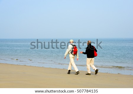Two men in casual clothes and walking shoes walking, talkin and gesticulating along the shoreline of the Dutych North Sea. It is still early in the morning in the beginning of the spring season.