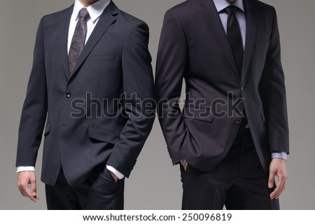 Two men in elegant suit on a dark background - stock photo