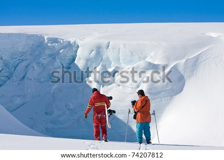Two men in front of a wall of snow - stock photo