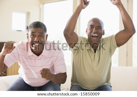 Two men in living room cheering and smiling - stock photo