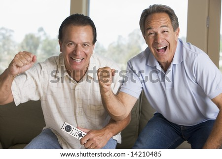 Two men in living room with remote control cheering and smiling - stock photo